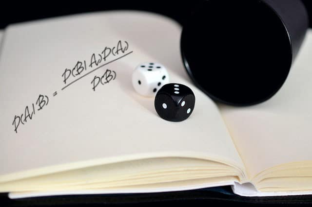 Bayes' theorem hand-written on a notebook. Additionally, two dice are rolled on top of the notebook from a black plastic cup.