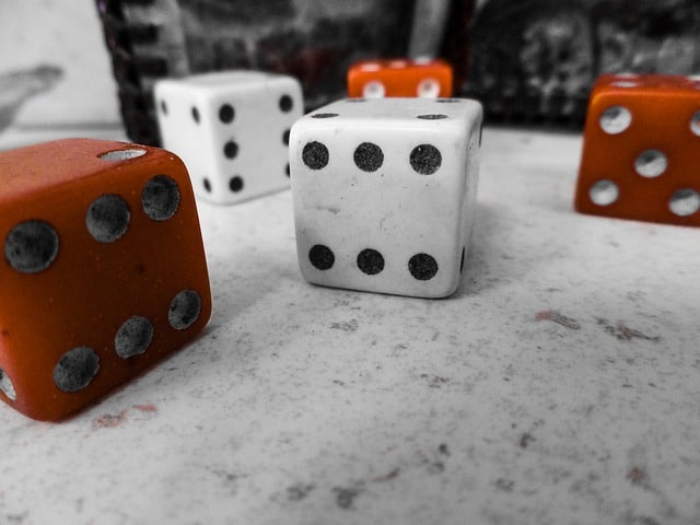 A photograph of two white and three brown large standard dice.