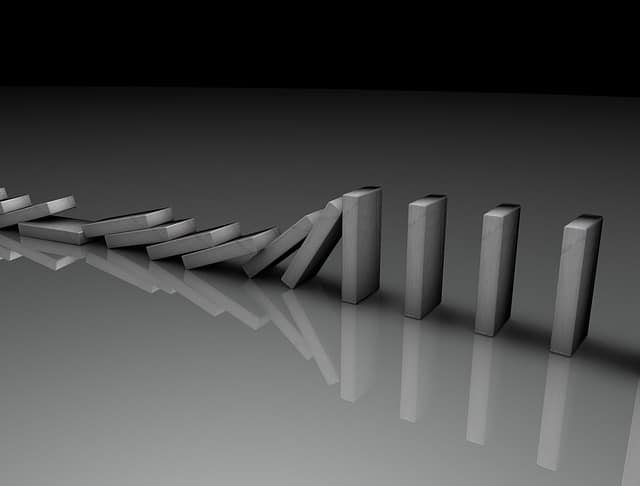 The domino effect illustrated with gray domino tiles in the process of falling one by one.
