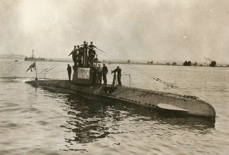 A photo of a Geman U-boat from WWI, half submerged in water with the crew on top