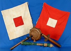 A white flag with a red square in the center, a red flag with a white square in the center, and torches