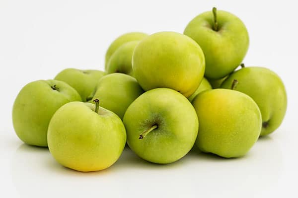 A picture of a pile of green apples