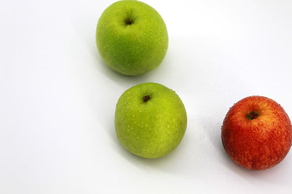 A picture of three apples (two green and one red)