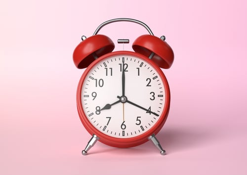Red vintage alarm clock on bright pink background in pastel colors