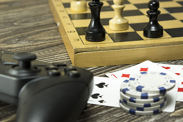 Gamepad, a chess board with figures and playing cards with the chips on the table. Focus on card