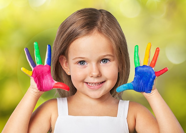 A smiling little girl showing ten painted fingers